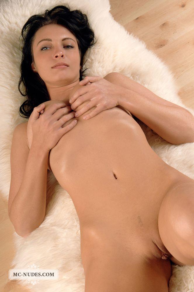 Грудастая брюнетка Lea Mcnudes лежит на полу, трогает обнаженную грудь и поднимает ножки