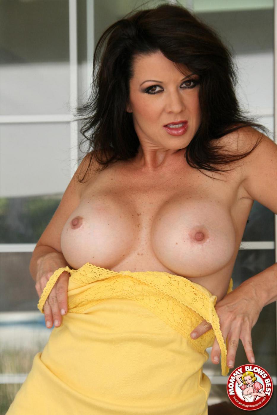 Мамочка-брюнетка с большой силиконовой грудью Raquel Devine снимает желтое платье и делает минет