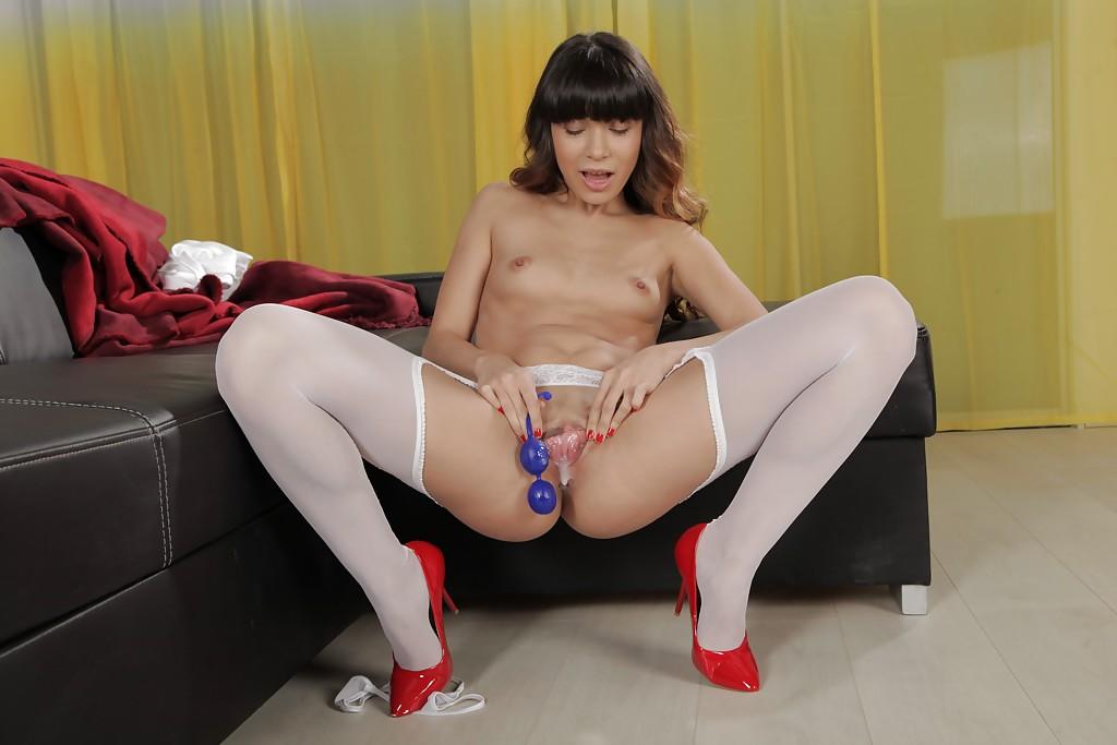 Молодая девушка худощавого телосложения дрочит синей игрушкой на диване