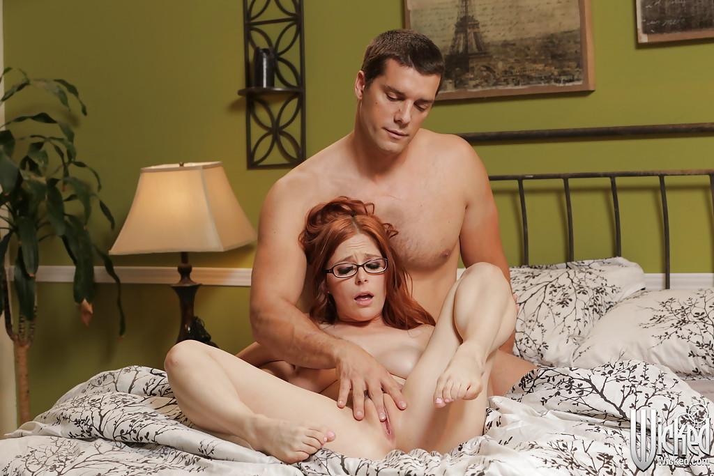 Рыжеволосая девушка в очках сосет член счастливчика на кровати