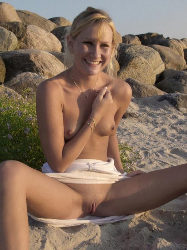 Голая веселая девушка ласкает себя на пляже