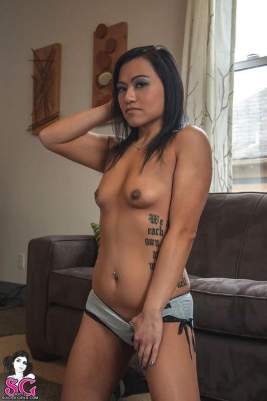 Красивая брюнетка с татуировками раздевается и позирует дома на диване