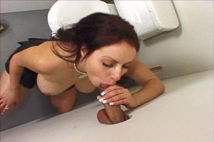 Девушка сидит на унитазе, когда через дырку в стене видит мужской член и принимается его сосать