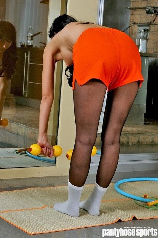 Брюнетка в спортзале с обнаженным торсом